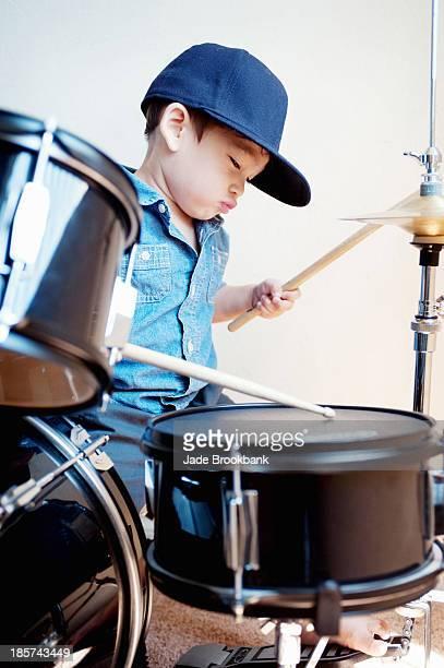 Male toddler playing drum kit