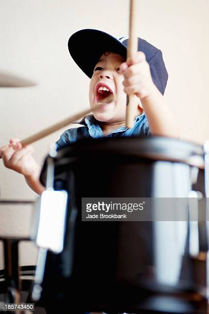 Male toddler playing on drum
