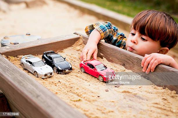 Male toddler reaching to play with toy cars in sandpit