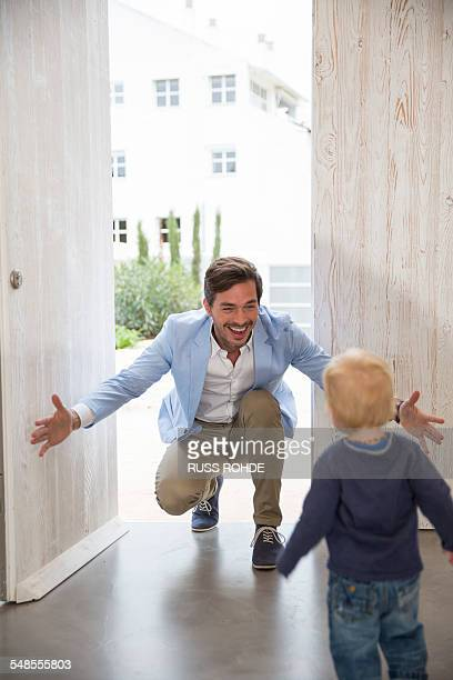 Male toddler running to fathers arms at front door