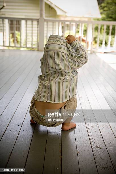 Male toddler (21-24 months) squatting on porch, rear view