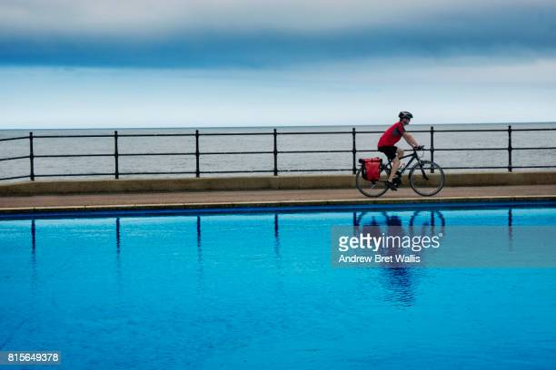 Male tour cyclist rides between the coastline and a paddling pool