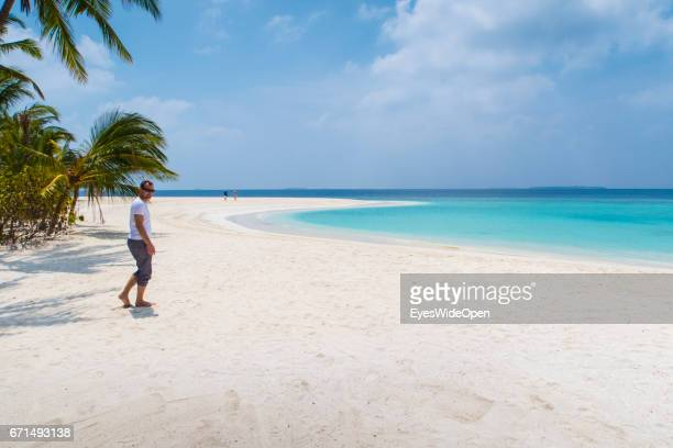 A male tourist is walking a the white sandy Beaches and cristal clear turquois Ocean at Milaidhoo Island BaaAtoll on February 20 2017 in Male Maldives