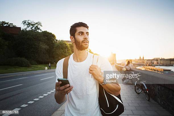 Male tourist looking away while walking on sidewalk of bridge