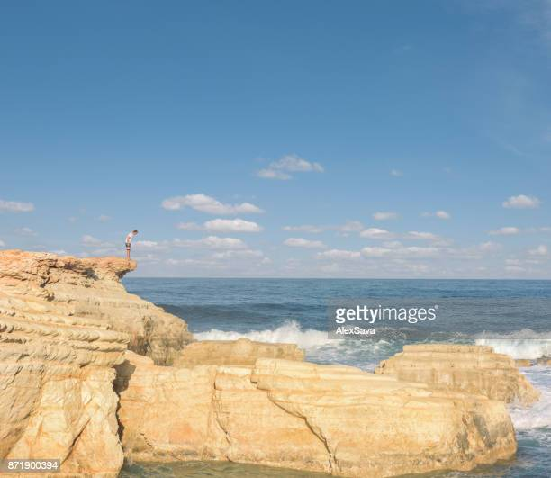 Male tourist standing on top of a cliff at the seaside