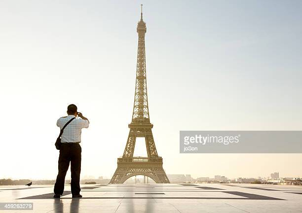 Male tourist taking photo of the Eiffel Tower