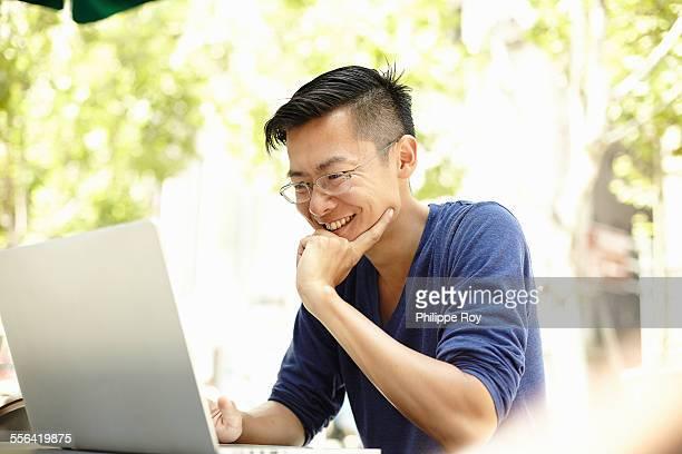 Male tourist using laptop at sidewalk cafe, The Bund, Shanghai, China