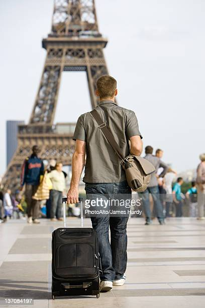 Male tourist walking with luggage, Eiffel Tower, Paris, France