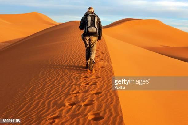 Macho turistas caminando en las dunas de arena, mañana, Mhamid, Marruecos
