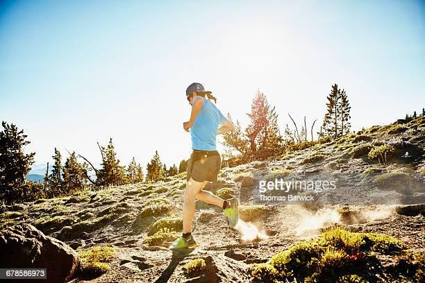 Male trail runner running down mountain trail