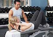 Male trainer working with mature woman on weight bench in gym