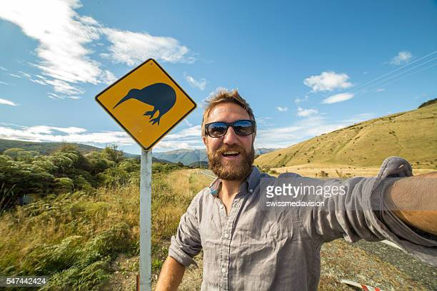 Male traveling takes selfie portrait with kiwi sign, New Zealand