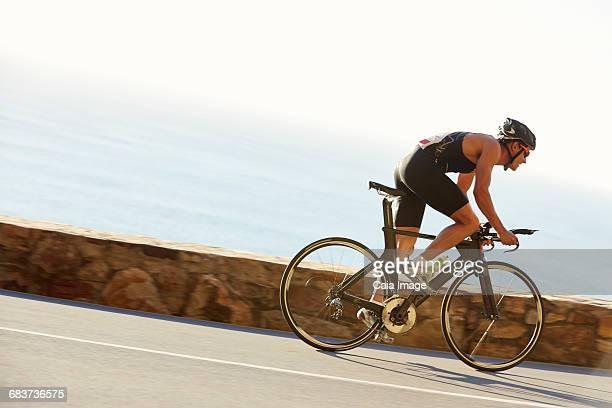 Male triathlete cyclist racing on ocean road
