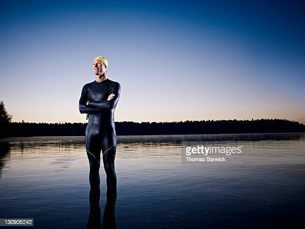 Male triathlete standing in water at sunrise