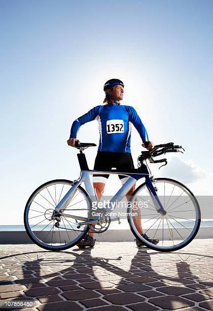 Male triathlete standing on road with bicycle