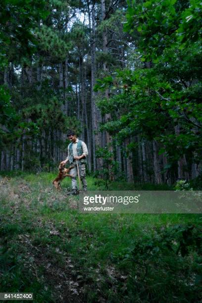 Male truffle hunter in 20's stops to pet his Cocker Spaniel dog affectionately in the woods, Abruzzo, Italy, Europe