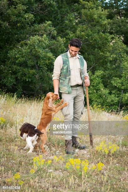 Male truffle hunter in his 20's pets his Cocker Spaniel dog that jumps up for affection and dog biscuit during a hunt in the woods on a summer day, Abruzzo, Italy, Europe