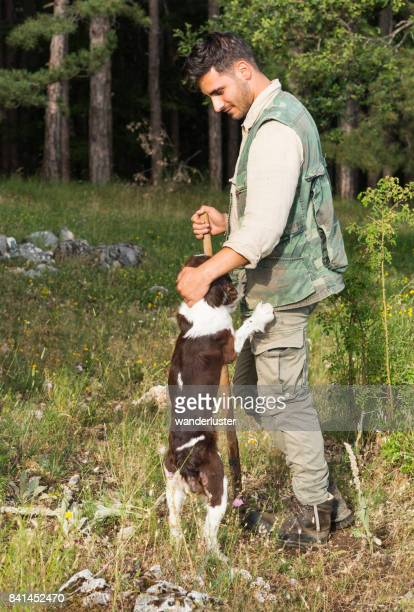 Male truffle hunter in his 20's pets his Springer Spaniel dog that jumped up for affection during a hunt in the woods on a summer day, Abruzzo, Italy, Europe