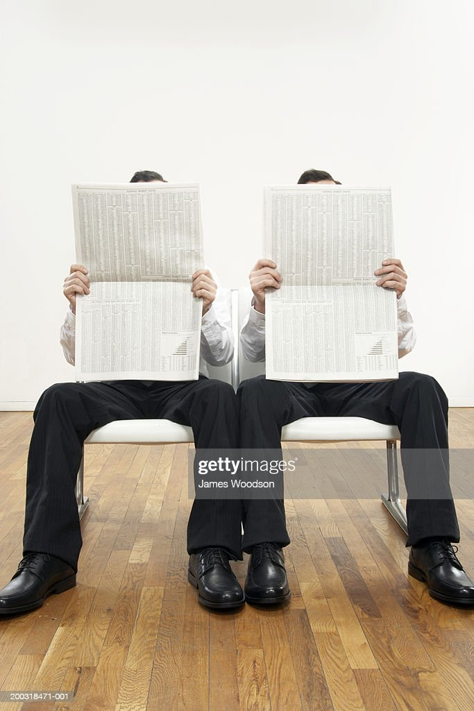 Male twins reading newspapers, faces obscured : Stock Photo