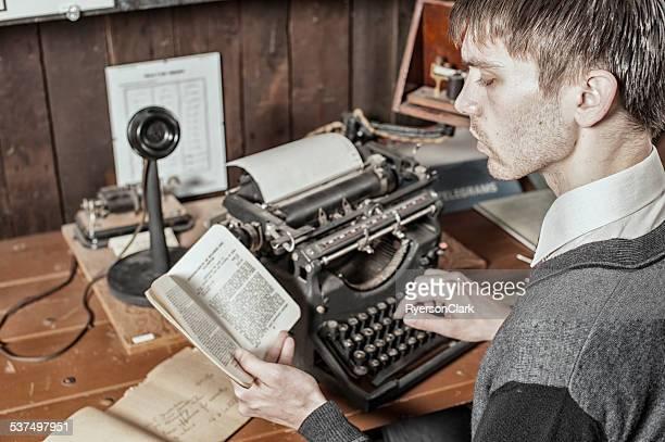 Homme dactylo sur une vieille machine à écrire.