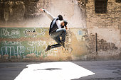Good looking male hip hop dancer jumping and performing in an abandoned building with graffiti walls