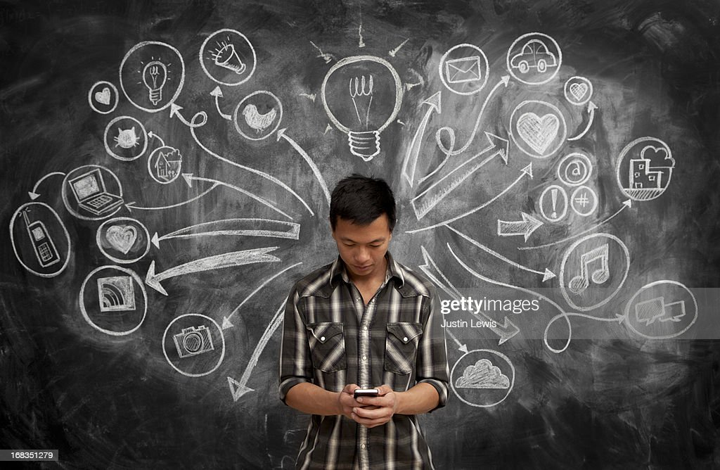 Male using phone by chalkboard w/social media icon : Stock Photo