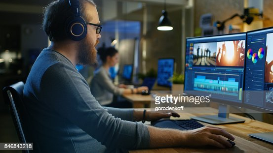 Male Videographer Edits and Cuts Footage and Sound on His Personal Computer, Puts on His Monitors/ Headphones. His Office is Modern and Creative Loft Studio. : Foto stock