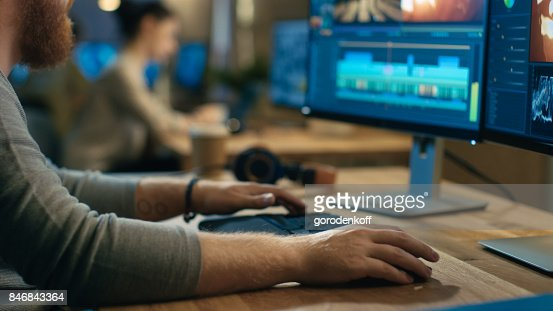 Male Videographer Edits and Cuts Footage and Sound on His Personal Computer with Two Displays. His Office is Modern and Creative Loft Studio. : Stock Photo