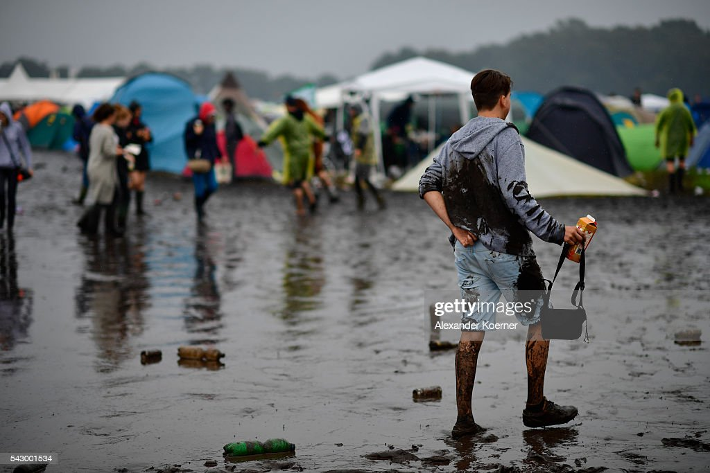 A male visitor walks the muddy and almost flooded camping compound at the Hurricane Festival compound on June 25, 2016 in Scheessel, Germany. The Hurricane Festival was evacuated yesterday and was delayed today for the late evening, following heavy rain and thunderstorm alerts. The rain and thunderstorm have hit the festival during the night and day, causing damage to tents and flooded the festival site, only 7 concerts can be played on two stages today. The Hurricane Festival celebrates this year its 25th anniversary. 75.000 music fans have visited the Festival, but some thousands have already left the compound due to the current situation.