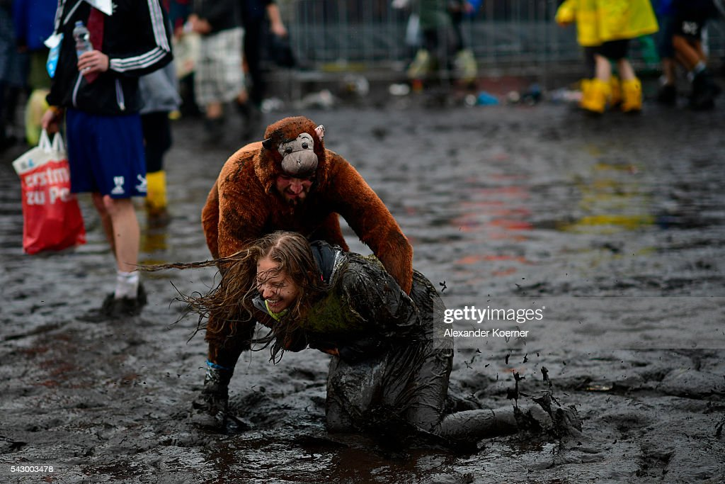 A male visitors dressed as a monkey plays with a female visitor in the mud at the muddy and flooded camping compound at the Hurricane Festival compound on June 25, 2016 in Scheessel, Germany. The Hurricane Festival was evacuated yesterday and was delayed today for the late evening, following heavy rain and thunderstorm alerts. The rain and thunderstorm have hit the festival during the night and day, causing damage to tents and flooded the festival site, only 7 concerts can be played on two stages today. The Hurricane Festival celebrates this year its 25th anniversary. 75.000 music fans have visited the Festival, but some thousands have already left the compound due to the current situation.