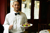 Male waiter standing in restaurant holding salad, smiling, portrait