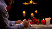 Male waiting lady for date in restaurant, scrolling on smartphone, time alone