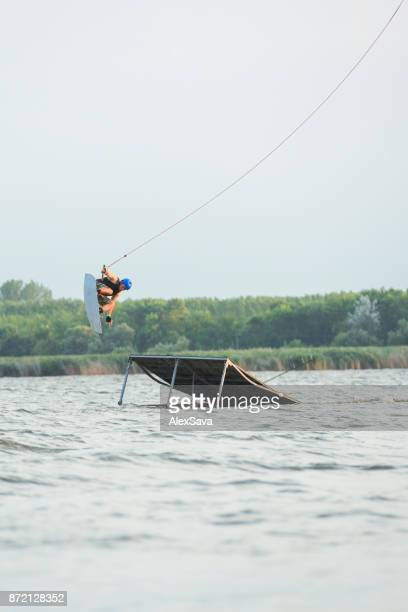 Male wakeboarder performing midair stunts jumping off ramp