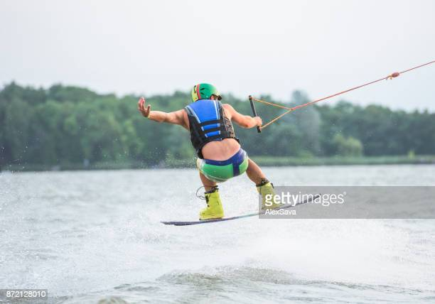 Male wakeboarder riding on lake