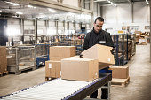 Male warehouse worker checking cardboard box from conveyor belt