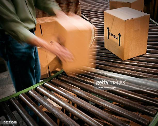 Male Warehouse Worker handing Cardboard Boxes and Conveyor Belt.