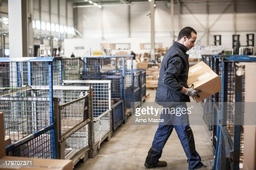 Male warehouse worker lifting cardboard box onto distribution trolley : Stock Photo