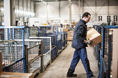 Male warehouse worker lifting cardboard box onto distribution trolley