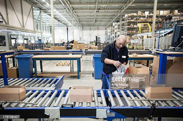 Male warehouse worker packing cardboard boxes for conveyer belt