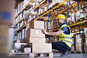 Young male warehouse worker with barcode scanner.