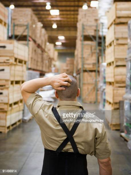 Male warehouse worker with hand on head
