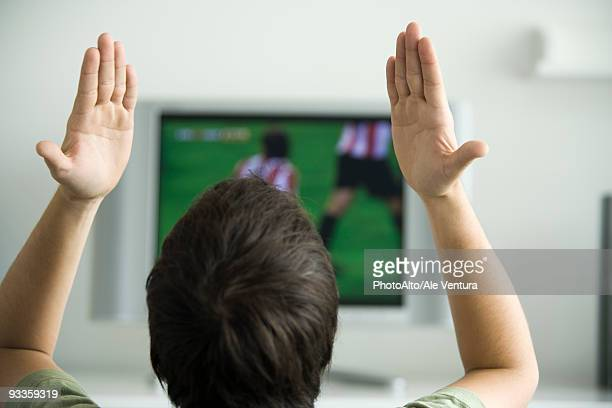 Male watching sports match on television, hands raised in air, rear view