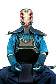 Male wearing a kendo armor with helmet and gloves, sitting position front view.