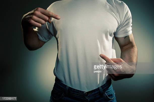 Male wearing a white T shirt and pointing to his chest