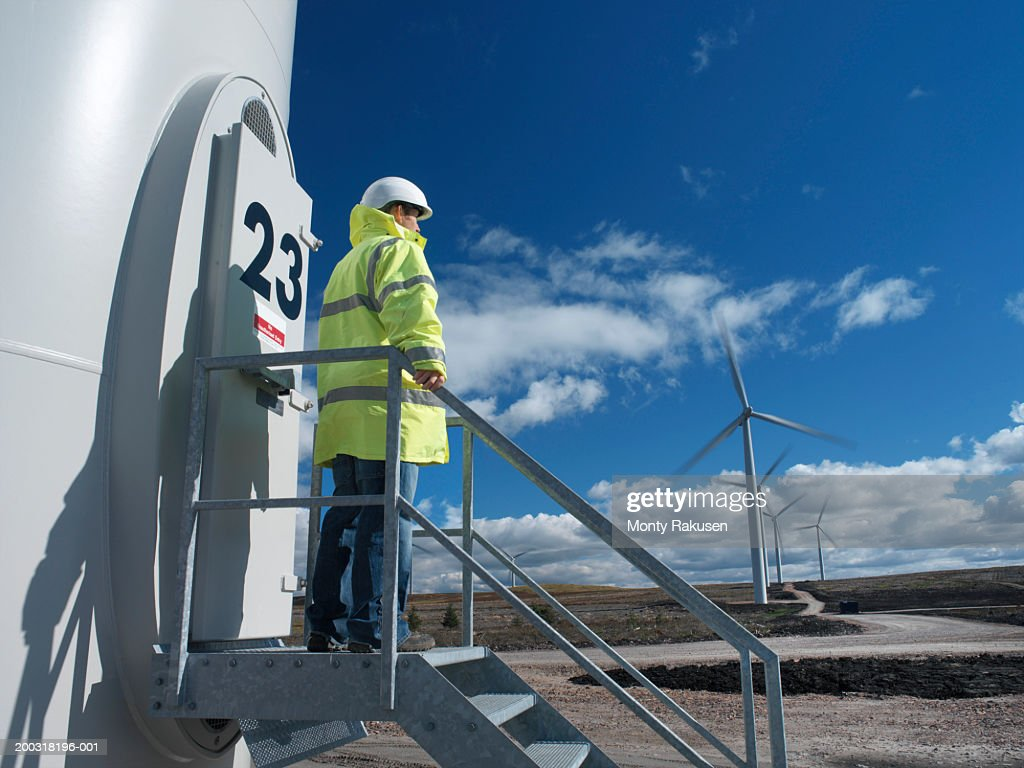 Male wind power plant worker standing on steps looking at wind farm : Stock Photo