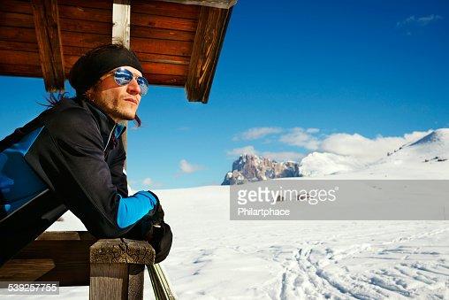 male winter sports athlete pausing in scenic alps landscape
