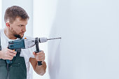 Handsome male with beard making a hole in white wall with a drill during interior finish