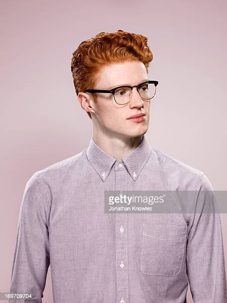 Male with wavy red hair and glasses, looking away