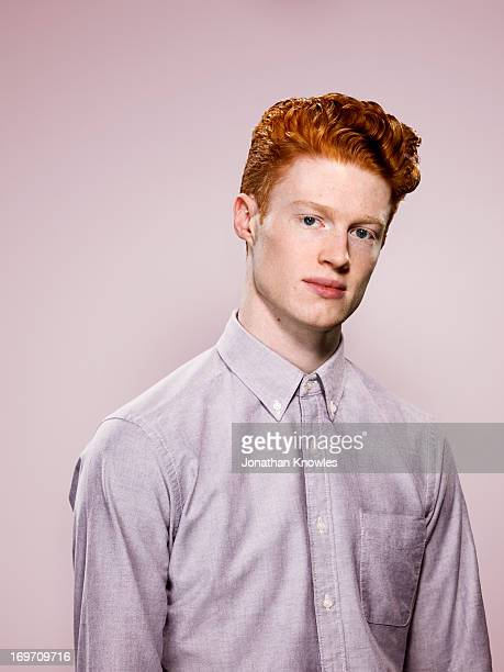 Male with wavy red hair looking into camera