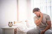 Male woke up by alarm clock having neck pain from sleeping